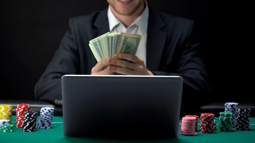 お札を持ちながらオンラインカジノをする男性