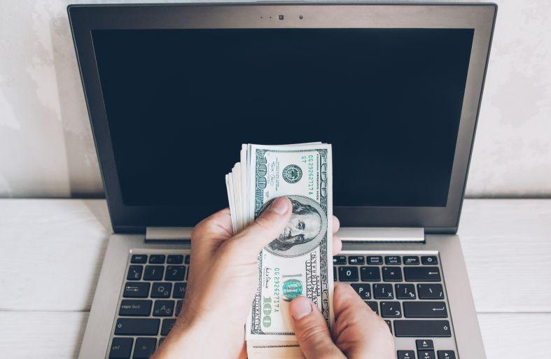 ノートパソコンとドル紙幣