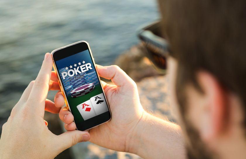 スマートフォンでポーカーを楽しむ男性