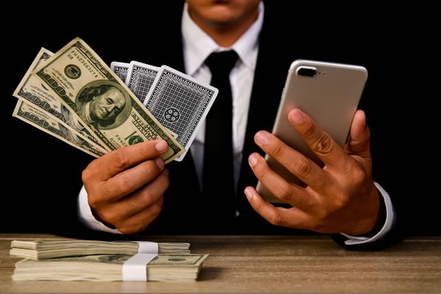 ドル札とカードとスマホを持つ男性