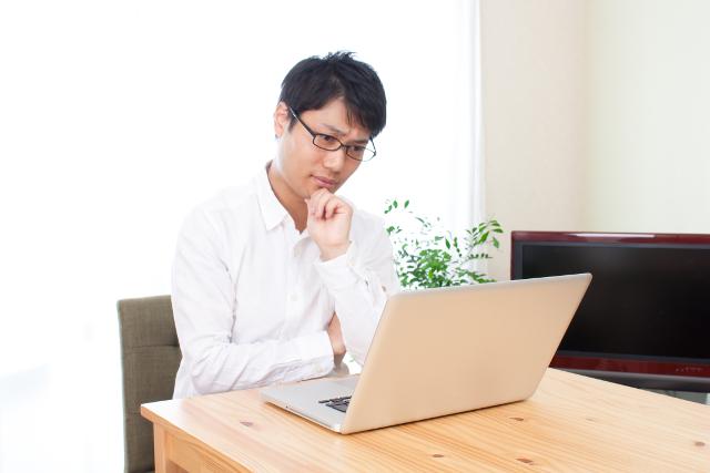 パソコンを見て悩む男性