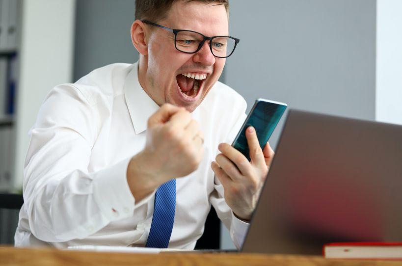 パソコンとスマホを見て喜ぶ男性