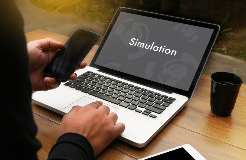 パソコンとスマホでシュミレーションする男性