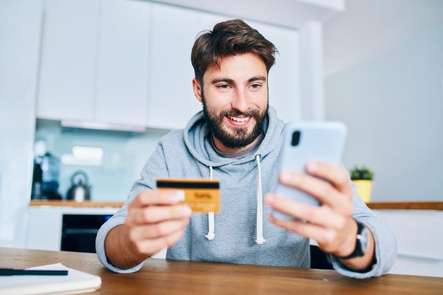 スマホとカードを持つ男性