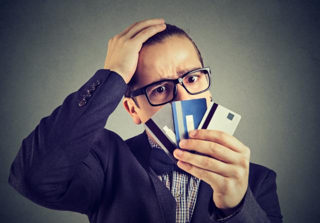 クレジットカードを見て考える男性