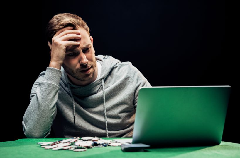 オンラインカジノに負けて頭を抱える男性