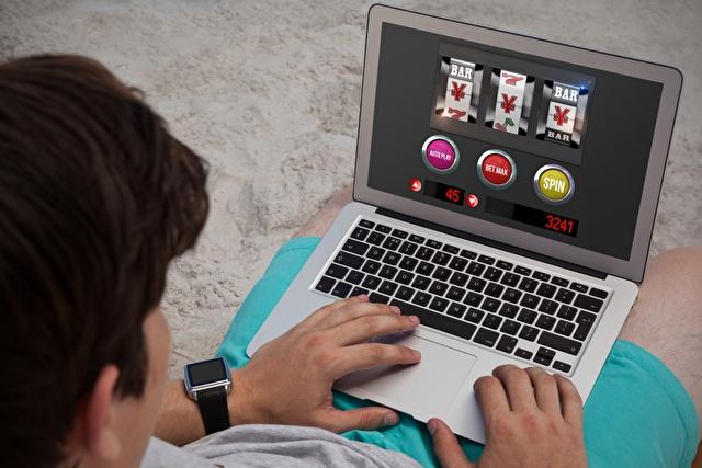 オンラインカジノのスロットをする男性
