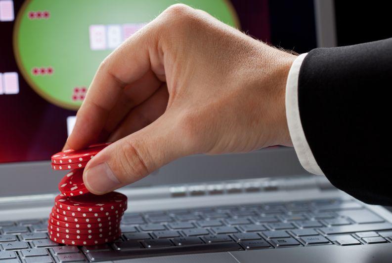 パソコンでオンラインカジノに賭ける男性の手