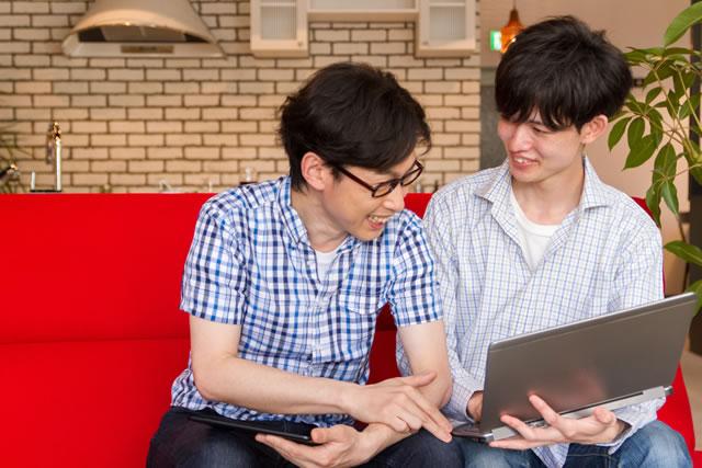 パソコンを見る男性2人
